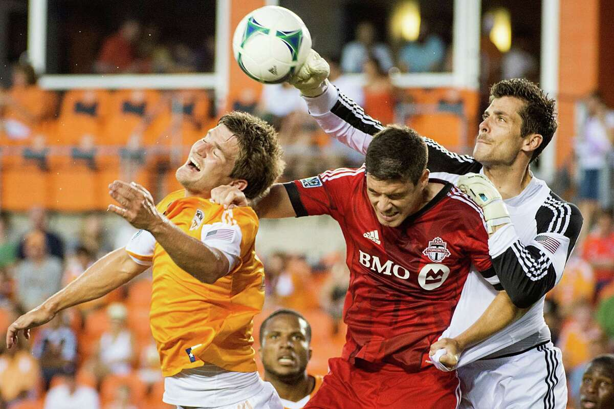 Houston Dynamo goalkeeper Tally Hall punches the ball away from Toronto FC defender Darren O'Dea as defender Bobby Boswell, left, closes in during the first half on Saturday, June 22, 2013, at BBVA Compass Stadium in Houston.