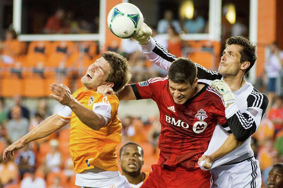 Houston Dynamo goalkeeper Tally Hall punches the ball away from Toronto FC defender Darren O'Dea as defender Bobby Boswell, left, closes in during the first half on Saturday, June 22, 2013, at BBVA Compass Stadium in Houston. Photo: Smiley N. Pool, Houston Chronicle / © 2013  Houston Chronicle