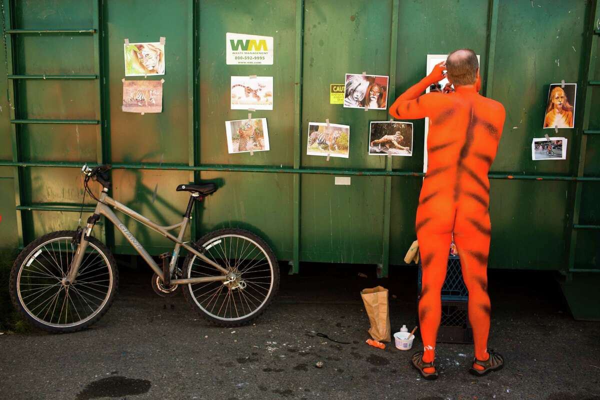 Naked bicycle riders prep at a paint party.