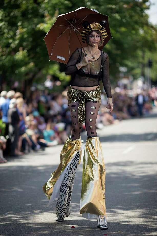 Stilt-walkers entertain the thousands lining the street. Photo: JORDAN STEAD, SEATTLEPI.COM / SEATTLEPI.COM