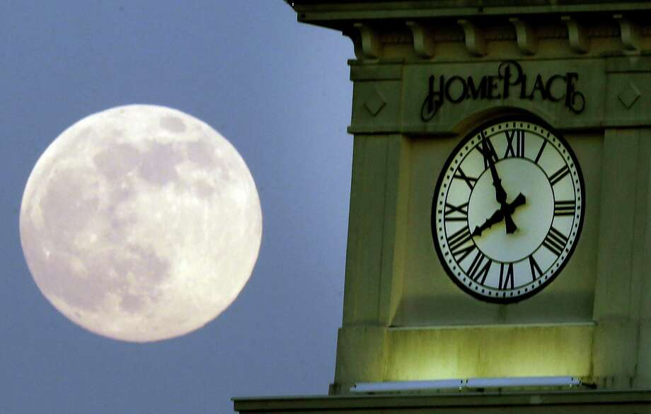 "A ""supermoon"" rises behind the Home Place clock tower in Prattville, Ala., Saturday, June 22, 2013. The biggest and brightest full moon of the year graces the sky early Sunday as our celestial neighbor swings closer to Earth than usual. While the moon will appear 14 percent larger than normal, sky watchers won't be able to notice the difference with the naked eye. Still, astronomers say it's worth looking up and appreciating the cosmos. (AP Photo/Dave Martin) Photo: Dave Martin, Associated Press / AP"