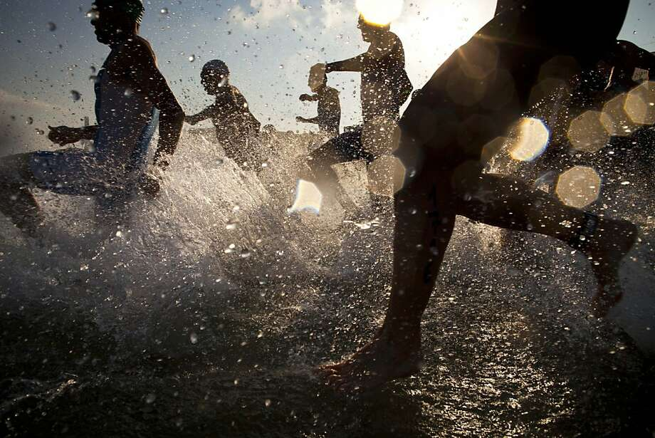 Athletes run into the Mediterranean Sea at the beginning of the Tel Aviv Triathlon in Tel Aviv, Israel, Saturday, June 22, 2013. (AP Photo/Oded Balilty) Photo: Oded Balilty, Associated Press