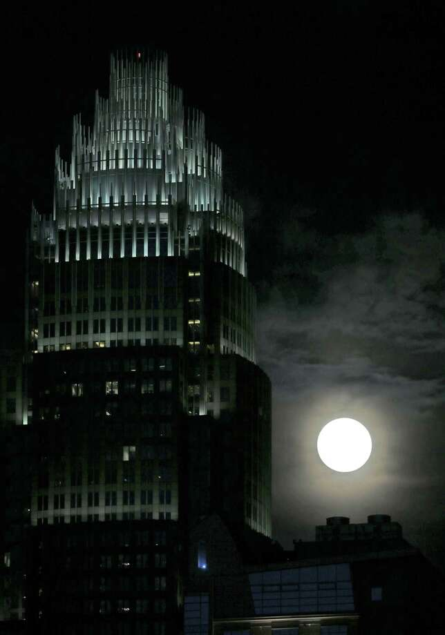 """A full moon rises beside the Bank of America corporate headquarters in downtown Charlotte, N.C., Saturday, June 22, 2013. The larger than normal moon called the """"Supermoon"""" happens only once this year as the moon on its elliptical orbit is at its closest point to earth.(AP Photo/Chuck Burton) Photo: Chuck Burton, Associated Press / AP"""