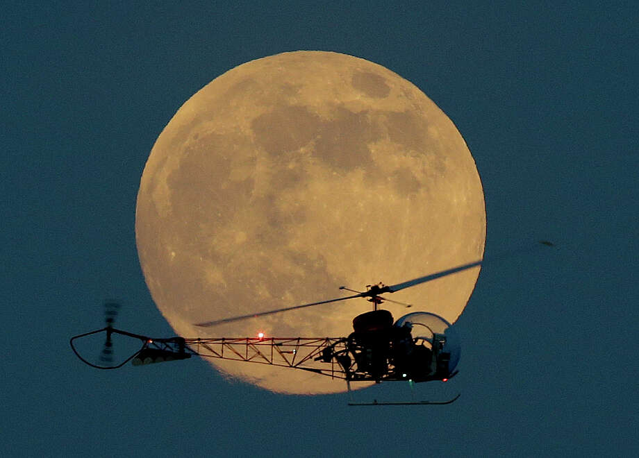 The moon is seen in its waxing gibbous stage as it rises behind the helicopter from the original Batman television show, which people can ride at the New Jersey State Fair, Saturday, June 22, 2013, in East Rutherford, N.J. The moon, which will reach its full stage on Sunday, is expected to be 13.5 percent closer to earth during a phenomenon known as supermoon. (AP Photo/Julio Cortez) Photo: Julio Cortez, Associated Press / AP