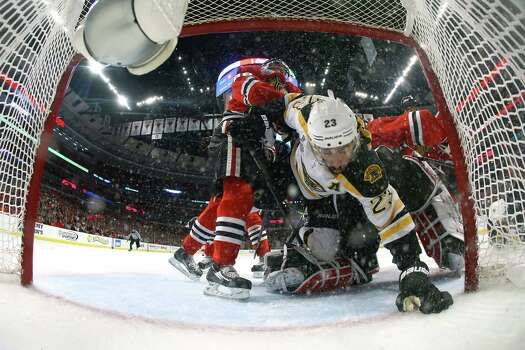 CHICAGO, IL - JUNE 22:  Chris Kelly #23 of the Boston Bruins trips over Corey Crawford #50 of the Chicago Blackhawks in the net during Game Five of the 2013 NHL Stanley Cup Final at United Center on June 22, 2013 in Chicago, Illinois. Photo: Bruce Bennett, Getty Images / 2013 Getty Images