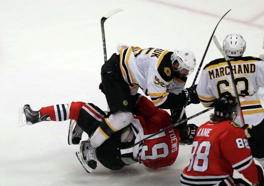 The Chicago Blackhawks' Jonathan Toews (19) takes a hit from the Boston Bruins' Johnny Boychuk (55) in the second period in Game 5 of the NHL Finals on Saturday, June 22, 2013, at the United Center in Chicago, Illinois. The Blackhawks won, 3-1, to take a 3-2 series advantage. (Chris Sweda/Chicago Tribune/MCT) Photo: Chris Sweda, McClatchy-Tribune News Service / Chicago Tribune