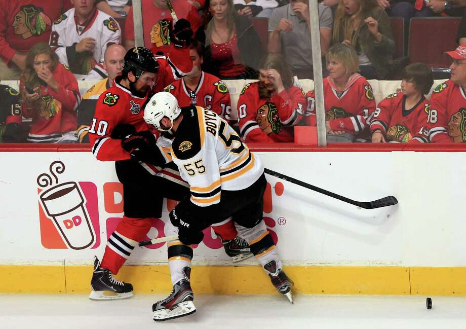CHICAGO, IL - JUNE 22:  Patrick Sharp #10 of the Chicago Blackhawks pushes Johnny Boychuk #55 of the Boston Bruins along the boards in Game Five of the 2013 NHL Stanley Cup Final at United Center on June 22, 2013 in Chicago, Illinois. Photo: Jamie Squire, Getty Images / 2013 Getty Images