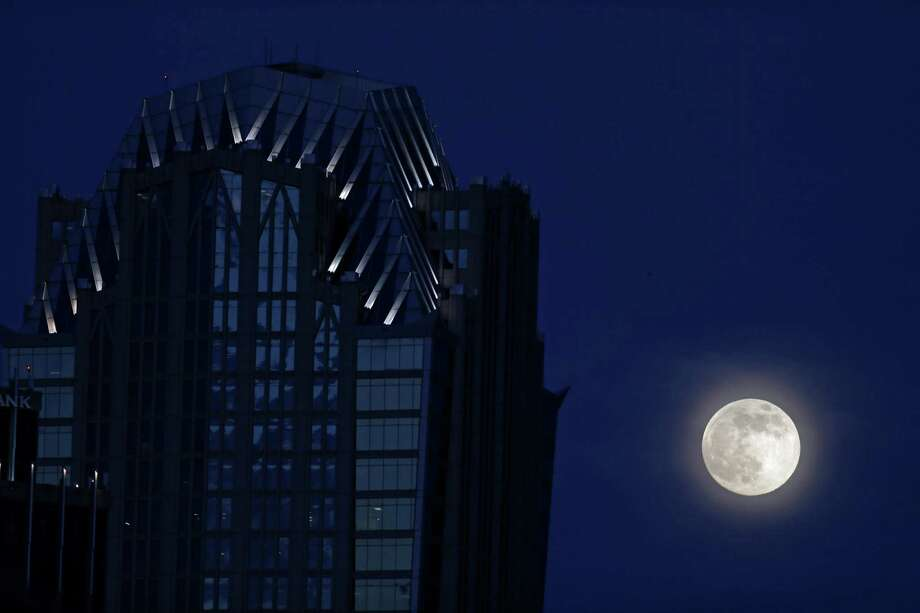 "A full moon rises beside an office building in downtown Charlotte, N.C., Saturday, June 22, 2013. The larger than normal moon called the ""Supermoon"" happens only once this year as the moon on its elliptical orbit is at its closest point to earth.(AP Photo/Chuck Burton) Photo: Chuck Burton, Associated Press / AP"