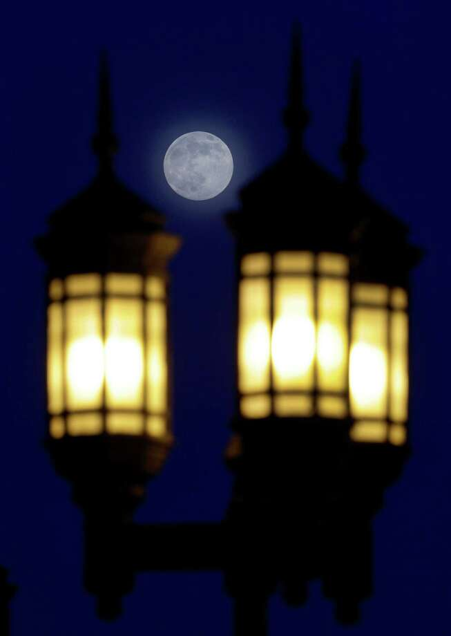 A full moon rises through a hazy sky over street lamps, Saturday, June 22, 2013, in Baltimore. The moon, which will reach its full stage on Sunday, is expected to be 13.5 percent closer to earth during a phenomenon known as supermoon. (AP Photo/Patrick Semansky) Photo: Patrick Semansky, Associated Press / AP