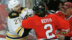 Boston Bruins center Chris Kelly (23) collides with Chicago Blackhawks defenseman Duncan Keith (2) in the third period during Game 5 of the NHL hockey Stanley Cup Finals, Saturday, June 22, 2013, in Chicago. (AP Photo/Charles Rex Arbogast)