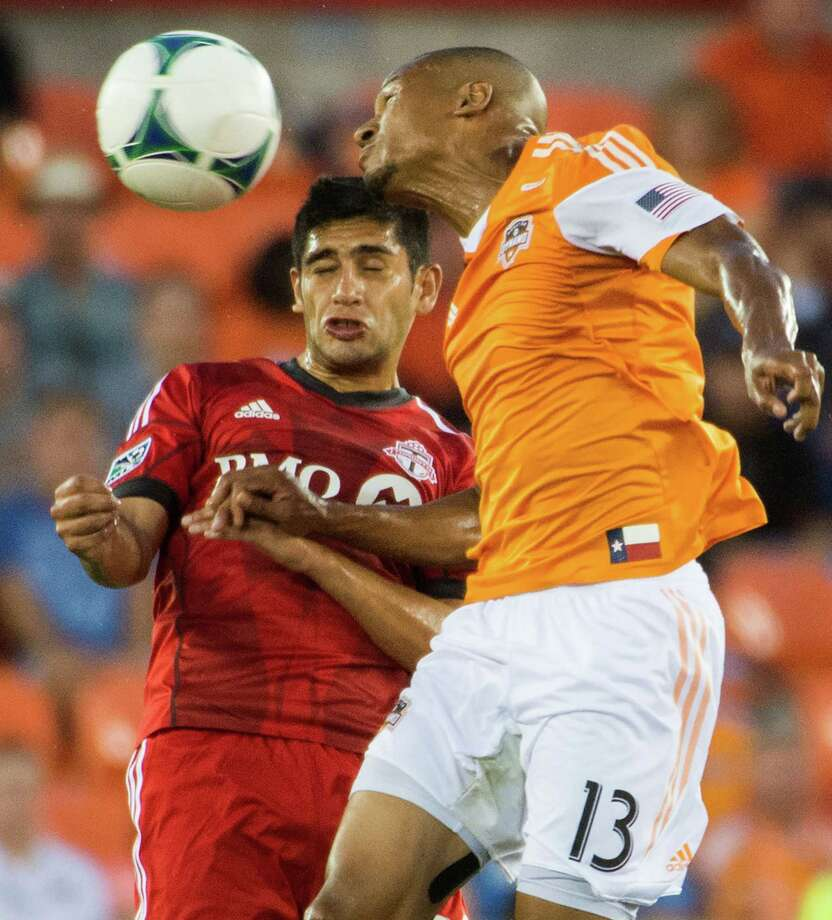 Houston Dynamo midfielder Ricardo Clark (13) wins a header from Toronto FC midfielder Matias Laba during the first half on Saturday, June 22, 2013, at BBVA Compass Stadium in Houston. Photo: Smiley N. Pool, Houston Chronicle / © 2013  Houston Chronicle