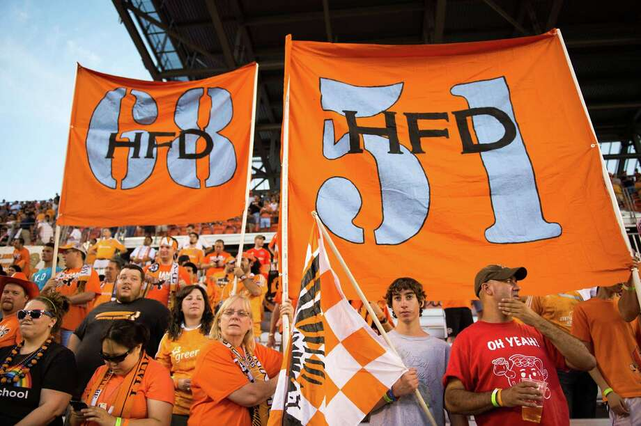 Houston Dynamo fans hold up signs in support of Houston Fire Department stations 51 and 68, two of the hardest hit by the deaths of four firefighters in motel fire in May, before a game against the Toronto FC on Saturday, June 22, 2013, at BBVA Compass Stadium in Houston. A five-alarm blaze on May 31 blaze left four Houston firefighters dead and 13 injured in was has been described as the deadliest in the history of the city's fire department. Photo: Smiley N. Pool, Houston Chronicle / © 2013  Houston Chronicle