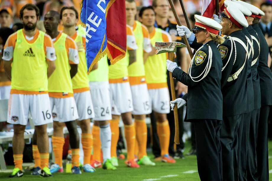 The Houston Fire Department Honor Guard displays the colors as Houston Dynamo players stand for the national anthem before a game against the Toronto FC on Saturday, June 22, 2013, at BBVA Compass Stadium in Houston. The team honored the firefighters during the game in recognition of a five-alarm blaze on May 31 blaze left four Houston firefighters dead and 13 injured in was has been described as the deadliest in the history of the city's fire department. Photo: Smiley N. Pool, Houston Chronicle / © 2013  Houston Chronicle