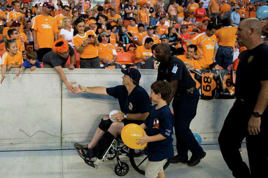 Houston Dynamo fans thank Houston firefighter Robert Yarborough before a game against the Toronto FC on Saturday, June 22, 2013, at BBVA Compass Stadium in Houston. The team honored the firefighters during the game in recognition of a five-alarm blaze on May 31 blaze left four Houston firefighters dead and 13 injured in was has been described as the deadliest in the history of the city's fire department. Photo: Smiley N. Pool, Houston Chronicle / © 2013  Houston Chronicle