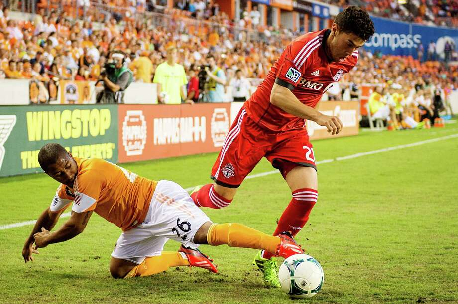 Houston Dynamo midfielder Corey Ashe (26) knocks the ball away from Toronto FC midfielder Jonathan Osorio (21) during the first half on Saturday, June 22, 2013, at BBVA Compass Stadium in Houston. Photo: Smiley N. Pool, Houston Chronicle / © 2013  Houston Chronicle
