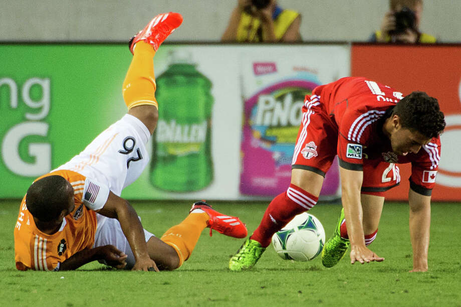 Houston Dynamo midfielder Corey Ashe (26) takes a tumble in a collision with Toronto FC midfielder Jonathan Osorio (21) during the first half on Saturday, June 22, 2013, at BBVA Compass Stadium in Houston. Photo: Smiley N. Pool, Houston Chronicle / © 2013  Houston Chronicle