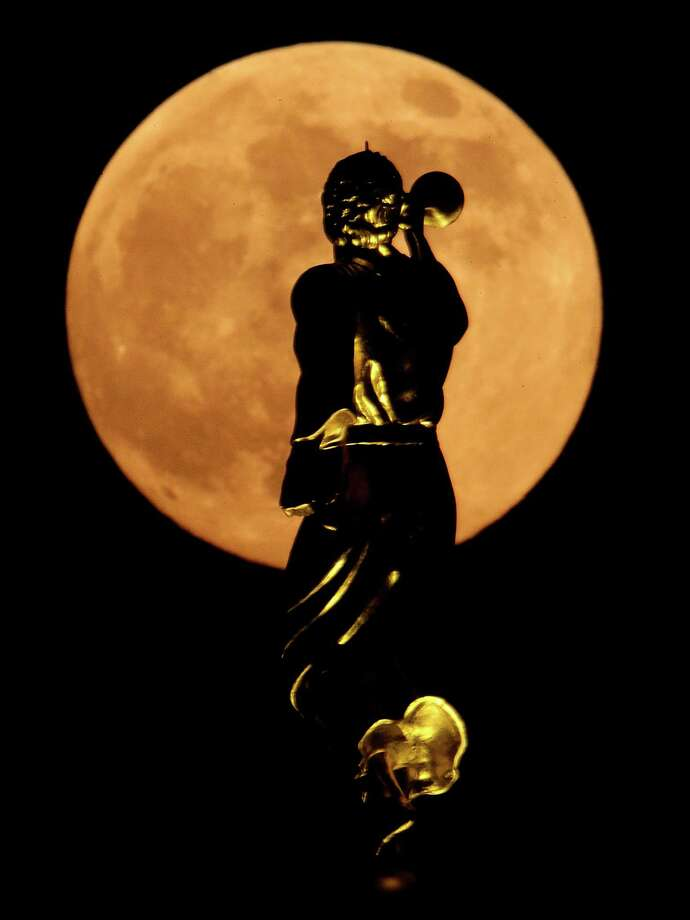 A statue of the Angel Moroni on top a Latter-day Saints temple is silhouetted against the rising moon Saturday, June 22, 2013, in Kansas City, Mo. The moon, which will reach its full stage on Sunday, is expected to be 13.5 percent closer to earth during a phenomenon known as supermoon. (AP Photo/Charlie Riedel) Photo: Charlie Riedel, Associated Press / AP