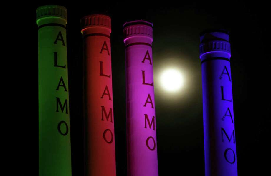 "A hazy ""supermoon"" is seen behind lighted smoke stacks at the Alamo Quarry Markey, formerly a cement factory, Saturday, June 22, 2013, in San Antonio. The biggest and brightest full moon of the year graces the sky early Sunday as our celestial neighbor swings closer to Earth than usual. While the moon will appear larger than normal, sky watchers won't be able to notice the difference with the naked eye.(AP Photo/Eric Gay) Photo: Eric Gay, Associated Press / AP"