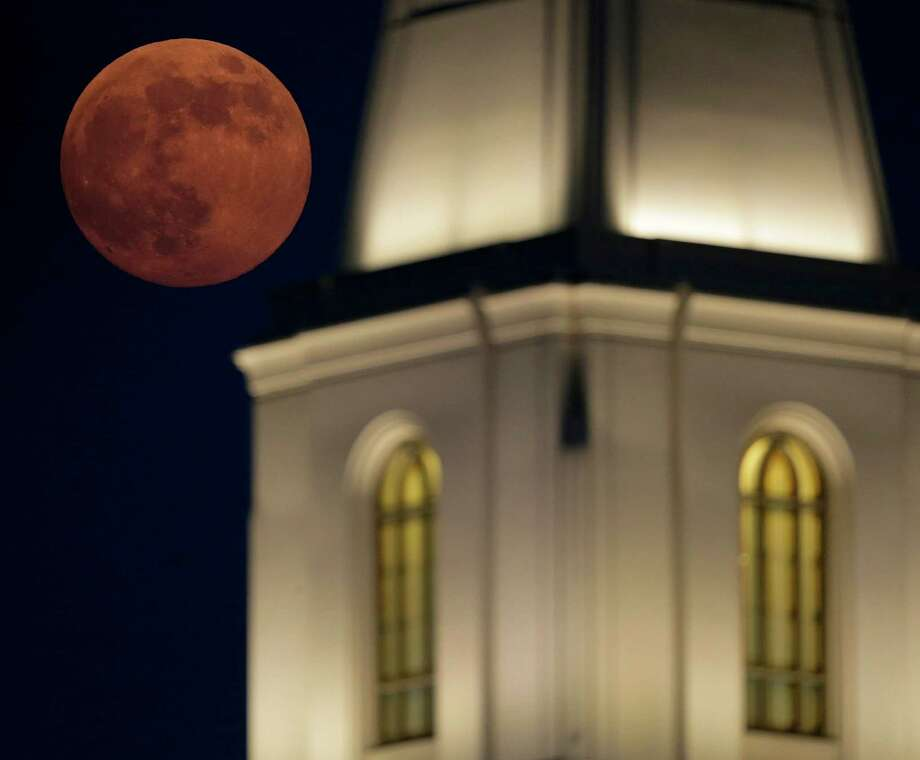 A full moon rises beyond a Latter-day Saints temple Saturday, June 22, 2013, in Kansas City, Mo. The moon, which will reach its full stage on Sunday, is expected to be 13.5 percent closer to earth during a phenomenon known as supermoon. (AP Photo/Charlie Riedel) Photo: Charlie Riedel, Associated Press / AP