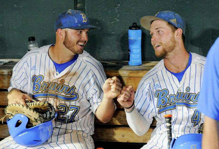 UCLA's Pat Gallagher (27) and Eric Filia (4) bump fists in the dugout after winning 4-1 against North Carolina in an NCAA College World Series baseball game in Omaha, Neb., Friday, June 21, 2013. (AP Photo/Francis Gardler) Photo: Francis Gardler
