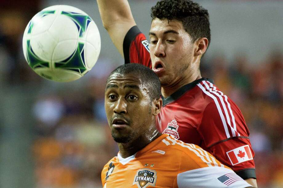 Houston Dynamo midfielder Corey Ashe and Toronto FC midfielder Jonathan Osorio fight for the ball during the first half on Saturday, June 22, 2013, at BBVA Compass Stadium in Houston. Photo: Smiley N. Pool, Houston Chronicle / © 2013  Houston Chronicle