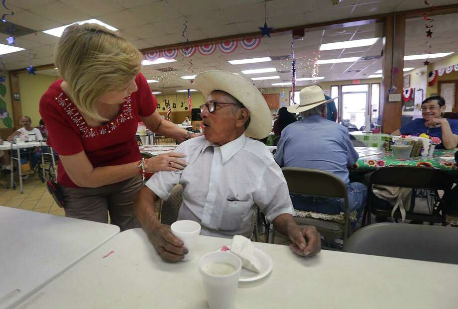 Sara Garza, owner of the Home Away From Home adult day care center in Penitas, chats with Medicaid managed care client Panchito Tovar, 81. Photo: Bob Owen / San Antonio Express-News