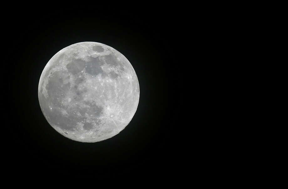 A full moon rises over Miami, Saturday, June 22, 2013. The moon, which will reach its full stage on Sunday, is expected to be 13.5 percent closer to earth during a phenomenon known as supermoon. (AP Photo/Alan Diaz) Photo: Alan Diaz, Associated Press / AP