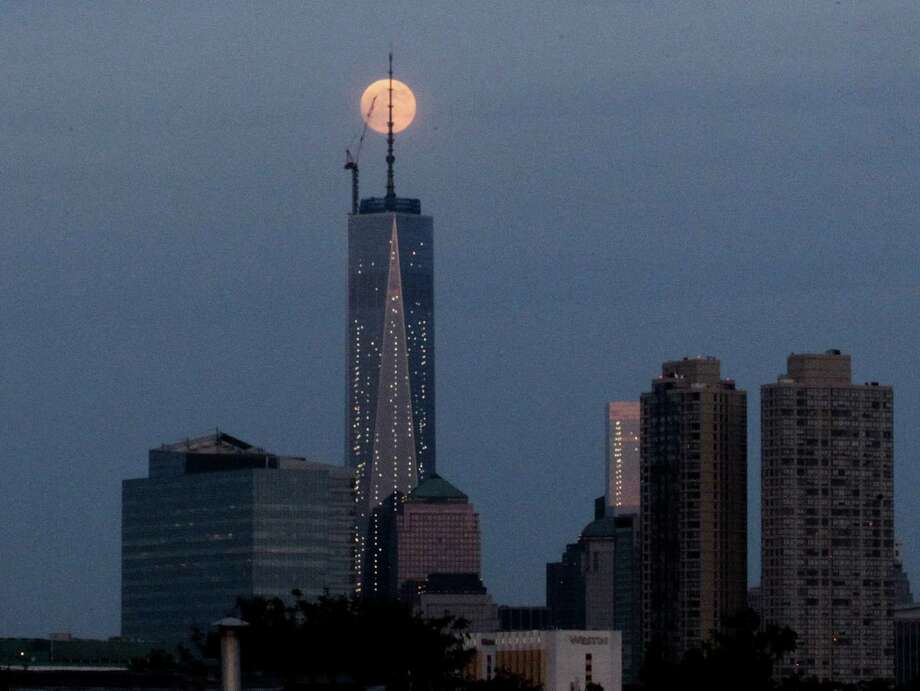 The moon is seen in its waxing gibbous stage as it rises over Lower Manhattan, including One World Trade Center, center, seen from The Heights neighborhood of Jersey City, N.J., Saturday, June 22, 2013. The moon, which will reach its full stage on Sunday, is expected to be seen 13.5 percent larger than usual during a phenomenon known as supermoon. (AP Photo/Julio Cortez) Photo: Julio Cortez, Associated Press / AP