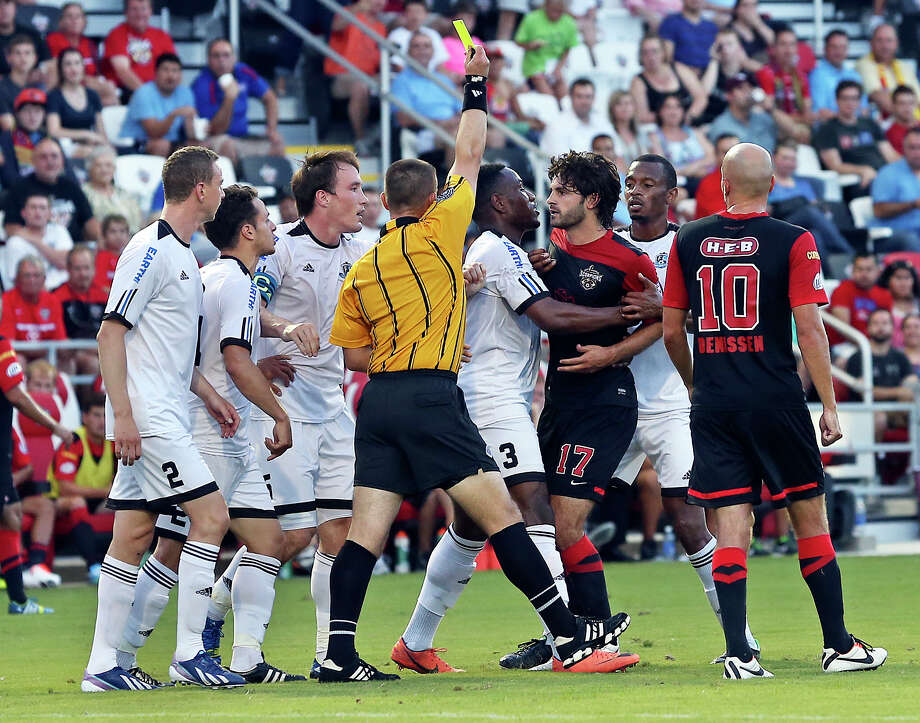 Blake Wagner is restrained as he receives the yellow card in the first half as the San Antonio Scorpions host FC Edmonton on June 22, 2013. Photo: For The San Antonio Express-News
