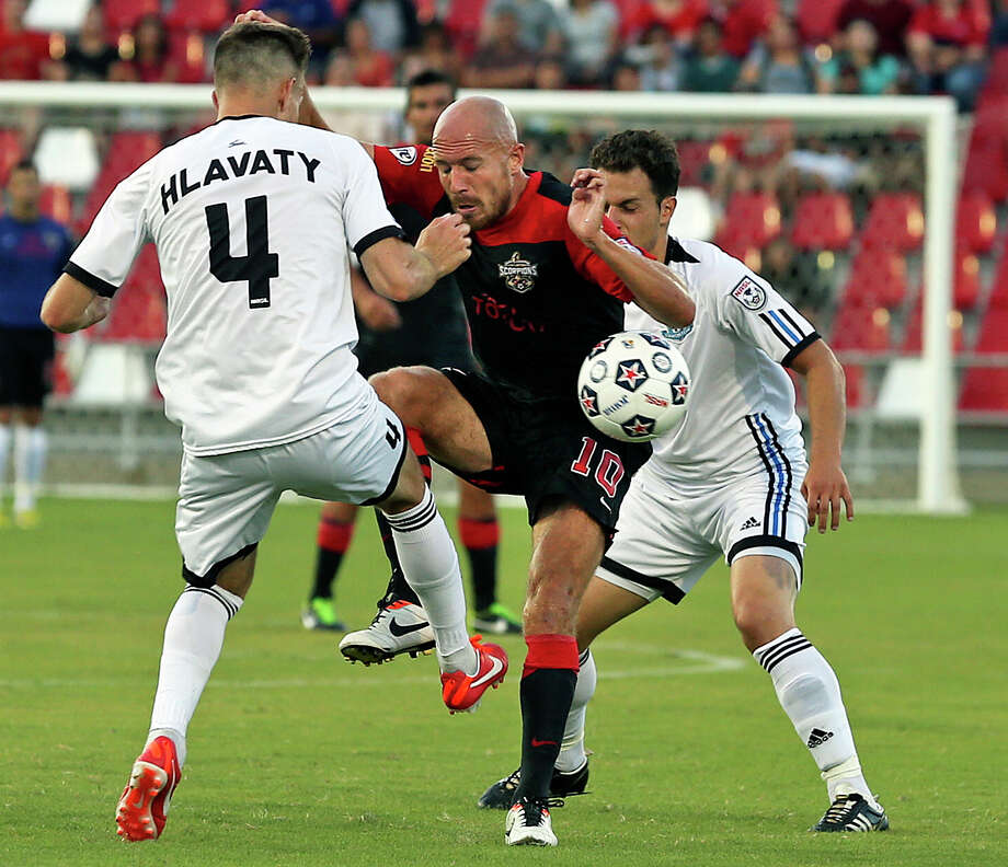 Hans Denissen squeezes the ball away from defenders as the San Antonio Scorpions host FC Edmonton on June 22, 2013. Photo: For The San Antonio Express-News
