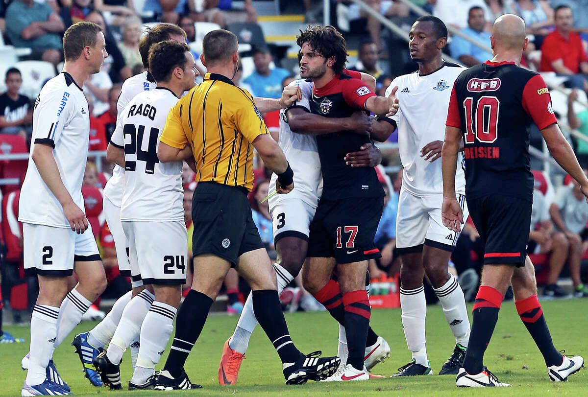 Blake Wagner is restrained as he receives the yellow card in the first half as the San Antonio Scorpions host FC Edmonton on June 22, 2013.