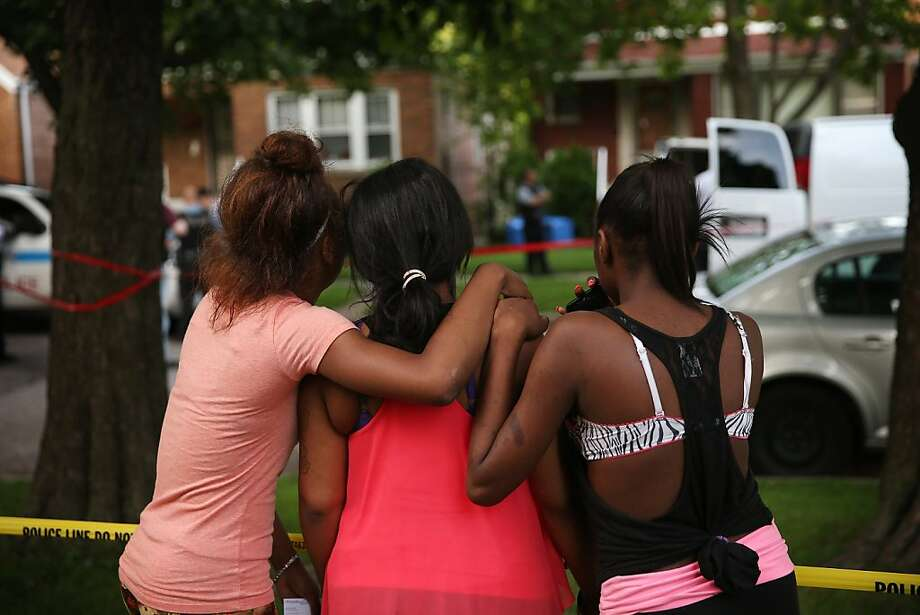 CHICAGO, IL - JUNE 22:  Young women watch as police prepare to remove the remains of their friend after he was shot and killed on June 22, 2013 in Chicago, Illinois. Two others were wounded in the shooting. There have been at least 29 homicides in Chicago during the first three weeks of June. More than 160 people have been shot and wounded in the city during the same period.  (Photo by Scott Olson/Getty Images) Photo: Scott Olson, Getty Images
