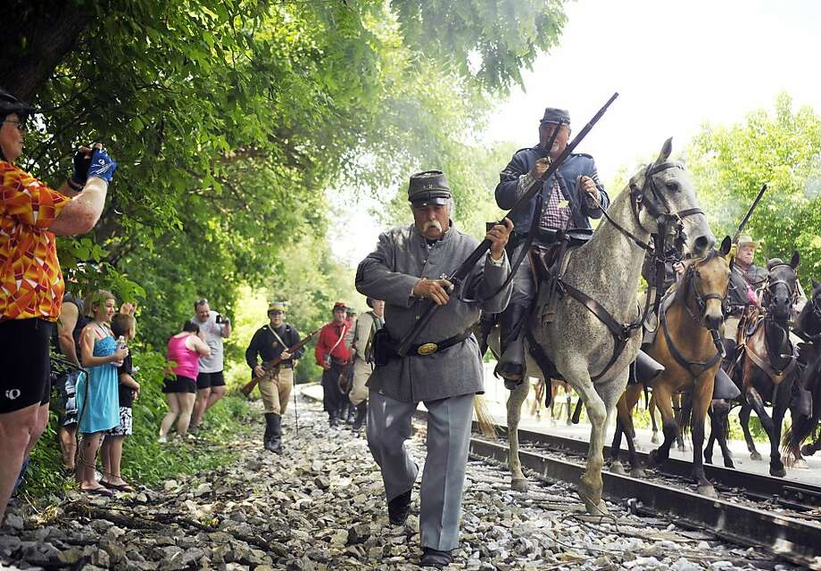 Re-enactors portraying Confederate cavalrymen and foot soldiers advance toward the Hanover Junction train station during a re-enactment of a raid made on the station in 1863 on Saturday, June 22, 2013 in North Codorus Township, Pa. The Friends of the Heritage Rail Trail Corridor and the York County Department of Parks and Recreation hosted a re-enactment of the Confederate Army's raid of the Hanover Junction train station. (AP Photo/York Daily Record, Chris Dunn)  Photo: Chris Dunn, Associated Press
