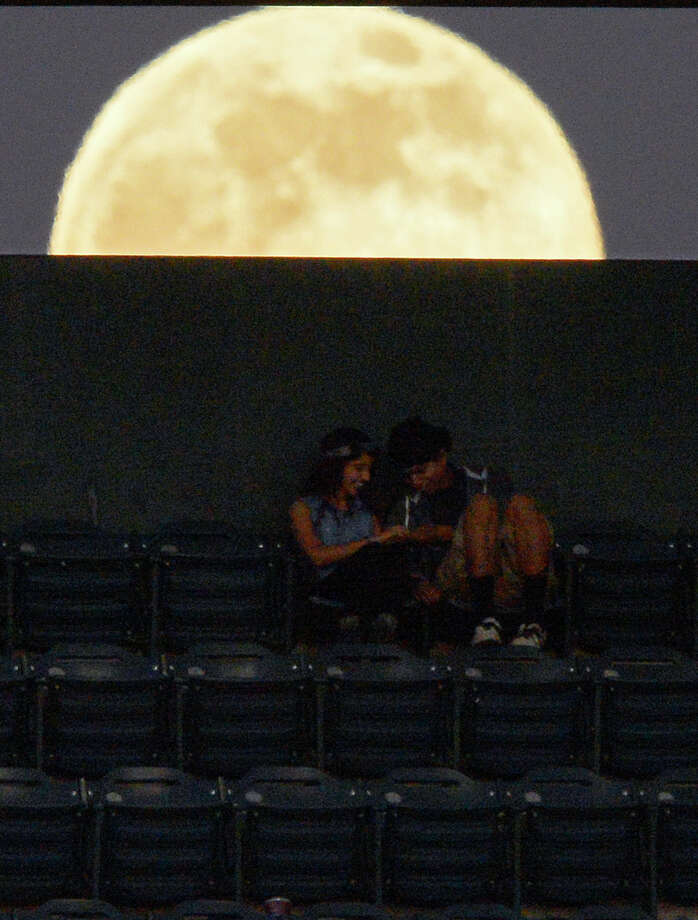 Fans sit as the moon rises behind them during the Los Angeles Angels' baseball game against the Pittsburgh Pirates, Saturday, June 22, 2013, in Anaheim, Calif.  (AP Photo/Mark J. Terrill) Photo: Mark J. Terrill, Associated Press / AP