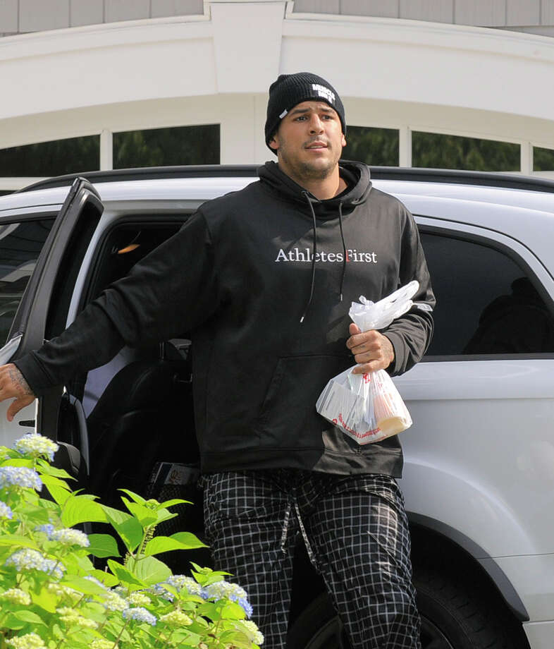 Aaron Hernandez returns to his home at Friday, June 21, 2013 in North Attleboro, Mass. At least one company yanked an endorsement deal from New England Patriots tight end Aaron Hernandez on Friday as puzzled family members of a friend found slain a mile from Hernandez's home sought answers about how he died.   BOSTON GLOBE OUT; METRO BOSTON OUT; MAGS OUT; ONLINE OUT; MANDATORY CREDIT Photo: The Boston Herald, Ted Fitzgerald