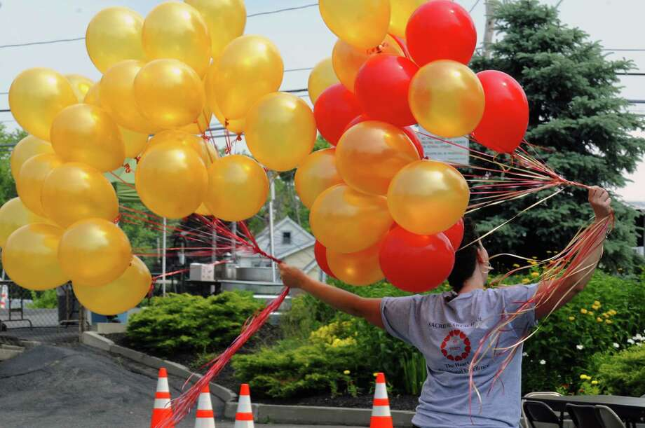 Maureen Lammon transports ballons for decoration during the Sacred Heart Church 100th anniversary celebration on Saturday June 22, 2013 in Troy, N.Y. (Michael P. Farrell/Times Union) Photo: Michael P. Farrell