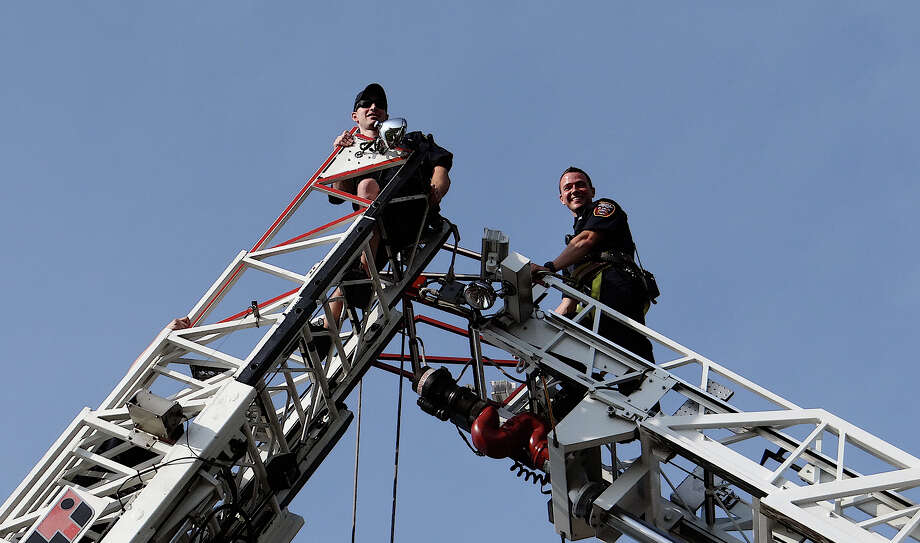 Fairfield firefighters at the top of aerial trucks' ladders to rig a large American flag that was unfurled over teh finish line for the Stratton Faxon Fairfield Half Marathon at Jennings Beach on Sunday. Photo: Mike Lauterborn / Fairfield Citizen