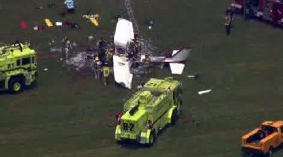 This frame grab from video provided by WDIV, WJBK, and WXYZ, shows emergency personnel examining a plane crash after a pilot and three passengers were killed shortly after takeoff from an airport northwest of Detroit in Waterford Township, Mich., on Friday, June 21, 2013. Three people aboard the private flight were killed instantly, while the fourth died later at a hospital. Photo: AP