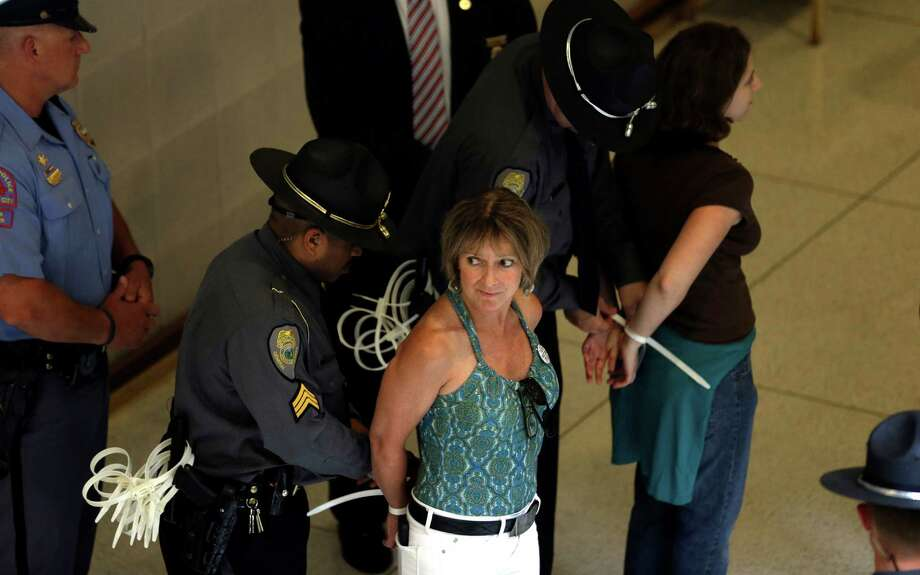 "Protestors are arrested outside the Senate chamber at the state legislature in Raleigh, N.C., Monday, June 17, 2013.  The National Association for the Advancement of Colored People and supporters of what the group calls ""Moral Mondays"" are outraged over GOP policies that they say restrict voting access, undermine public education and hurt the poor and jobless. Photo: AP"