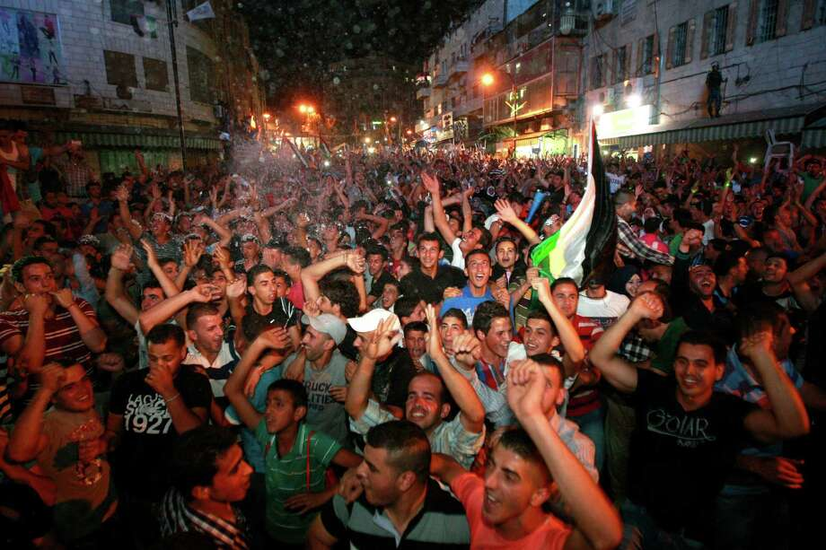 "Palestinians celebrate after Palestinian singer Mohammed Assaf won a regional TV singing contest, in the West Bank city of Ramallah, Saturday, June 22, 2013. Palestinians relished a rare moment of pride and national unity Saturday after the 23-year-old wedding singer from a refugee camp in the Gaza Strip won ""Arab Idol,"" a regional TV singing contest watched by millions of people. Photo: AP"