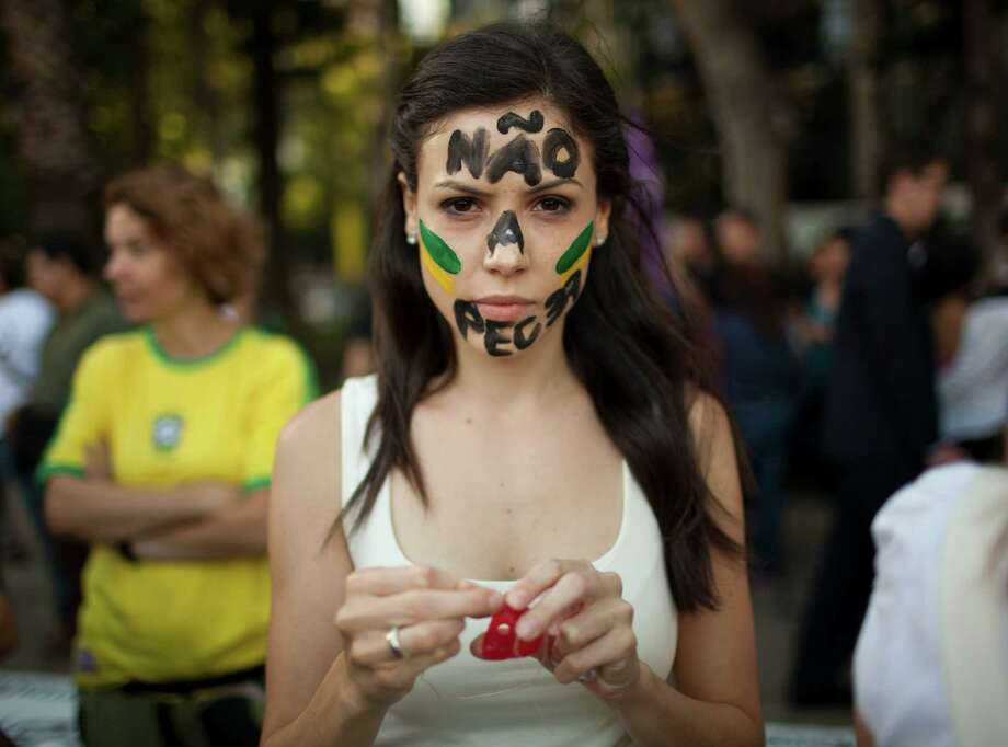 "Marcella Santiago whose face is painted with a message in Portuguese; ""No to PEC 37,"" prepares to put on a clown nose before joining protestors near the Angel of Independence monument in Mexico City, Tuesday, June 18, 2013. Brazilian nationals gathered to condemn the heavy tax burden in Brazil, corrupt politicians and woeful public education, health and transport systems. PEC 37 is a proposed constitutional amendment that limits the powers of the Public Ministry to investigate corruption and abuse. Some protestors wear a clown nose to symbolize the ""circus"" that they believe Brazil politics has become. Photo: AP"