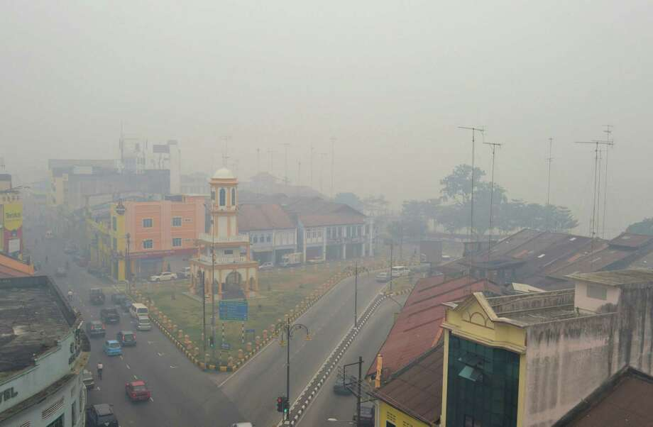 In this Saturday, June 22, 2013 photo, motorists make their way through a town covered with a thick haze in Muar, northwestern Johor, Malaysia. Malaysian authorities are declaring a state of emergency in the southern district of Muar where a smoky haze blamed on Indonesian forest fires has triggered one of the country's worst pollution levels. (AP Photo)  Photo: AP