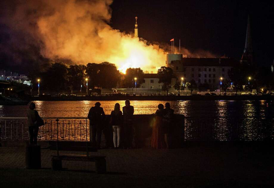 In this photo taken late Thursday, June 20, 2013, curious onlookers watch fire on the roof of Latvia's medieval Riga Castle, a museum and presidential residence, in Riga, Latvia . The Baltic News Service is reporting that a fire has partially damaged the Riga Castle, a medieval fortress that houses the National History Museum of Latvia. The castle normally serves as the presidential residence, but BNS says Latvian President Andris Berzins is staying elsewhere as the building is being renovated. Photo: AP