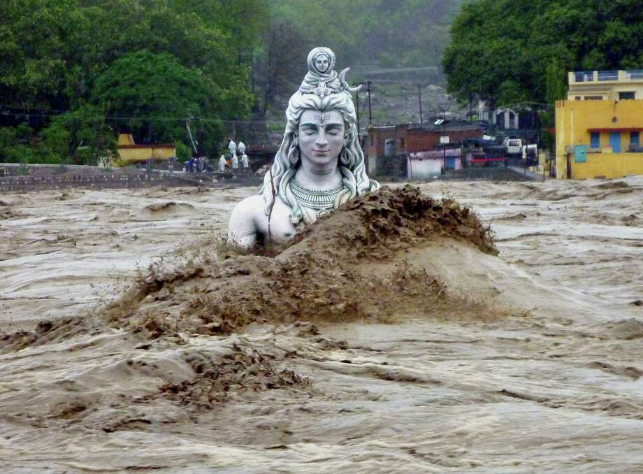 A submerged idol of Hindu Lord Shiva stands in the flooded River Ganges in Rishikesh, in the northern Indian state of Uttarakhand, India, Tuesday, June 18, 2013. Monsoon torrential rains have cause havoc in northern India leading to flash floods, cloudbursts and landslides as the death toll continues to climb and more than 1,000 pilgrims bound for Himalayan shrines remain stranded. Photo: AP