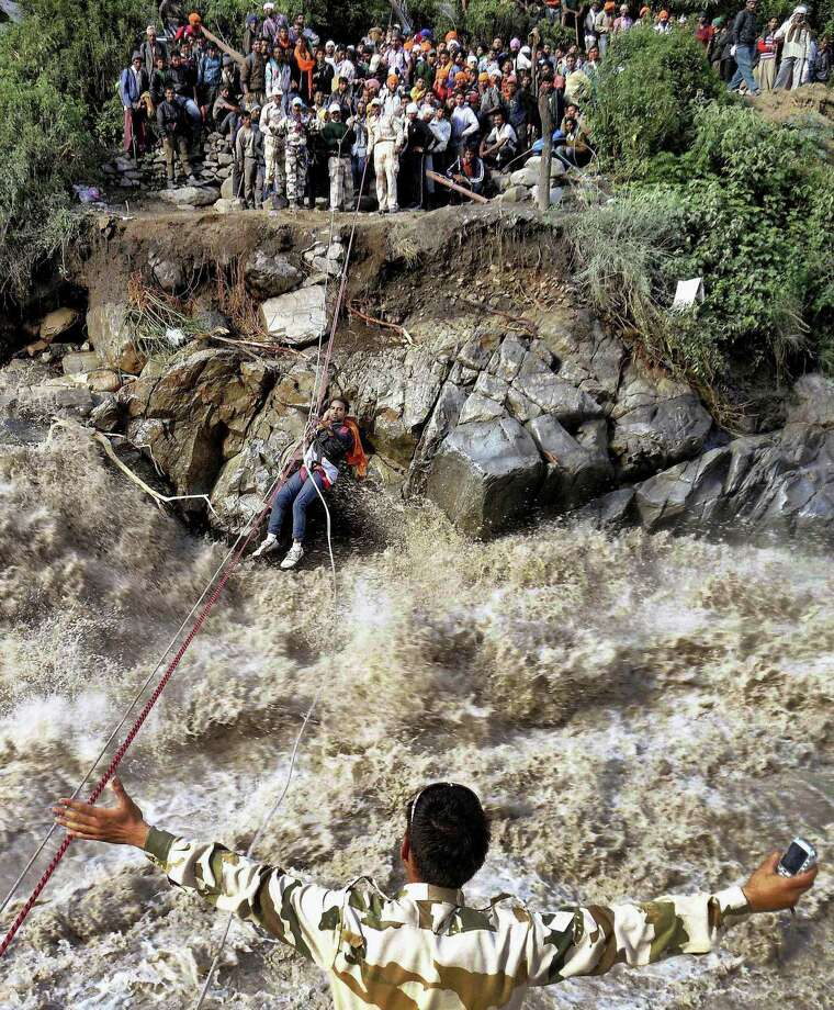 In this Thursday, June 20, 2013 photo, Indo-Tibetan Border Police (ITBP) use a rope to rescue stranded pilgrims cross a river swollen by flood waters at Govind Ghat, in Chamoli district, in northern Indian state of Uttarakhand, India. Uttrakhand spokesman Amit Chandola said the rescue operation centered on evacuating nearly 27,000 people trapped in the worst-hit Kedarnath temple area - one of the holiest Hindu temples dedicated to Lord Shiva, located atop the Garhwal Himalayan range. Photo: AP