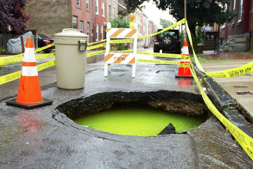 This June 2013 photo provided by Steven Reitz shows a sinkhole filled with a green ooze in the Northern Liberties section of Philadelphia. Gary Burlingame, director of labs for the Philadelphia Water Department, said the green hue is the result of harmless dye that's used to track flowing water in a bid to find out where a sinkhole forms.