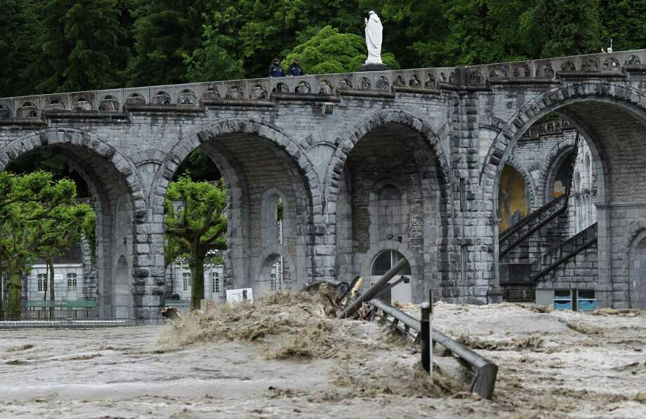 The sanctuary of Lourdes flooded, in Lourdes, southwestern France, Tuesday, June 18, 2013. French rescue services and police are evacuating hundreds of pilgrims from hotels threatened by floodwaters from a rain-swollen river in the Roman Catholic shrine town of Lourdes. Photo: AP