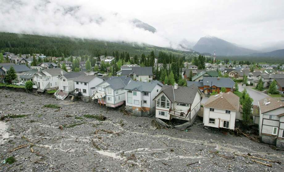 A row of homes are severely damaged by the flooded Cougar Creek in the mountain resort town of Canmore, Alberta on Friday June 21, 2013. Photo: AP