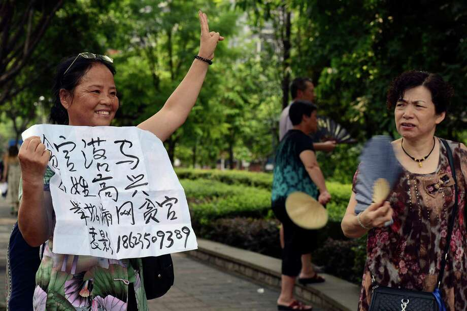 "In this June 19, 2013 photo, a woman holds up a sign which reads ""Corrupt official falls off the horse, Common People celebrate, Report on corrupt officials who fall through the net""  outside the court where the first trial of Lei Zhengfu, former Communist Party chief of a local district, who was involved in sex tape scandal, will be held in southwest China's Chongqing Municipality.  While the corruption trials of high-level officials typically look like the scripted outcome of behind-the-scenes bargaining, this case offers a rare look at what happens when a lower-level official is caught in a high-profile crackdown with few political cards to play. (AP Photo) Photo: AP"