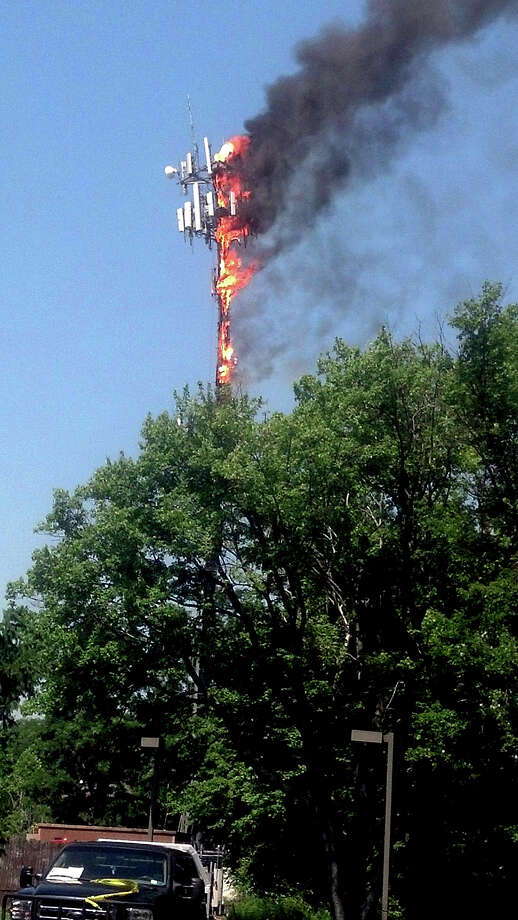 A cellphone tower burns at the Bensalem Municipal complex Friday, June 21, 2013 in Bensalem, Pa. A 75-foot-tall cellphone tower caught fire on Friday while work was being done on it and was leaning, prompting the evacuations of nearby homes. (AP Photo/Bucks County Courier Times, Jo Ciavaglia) Photo: AP